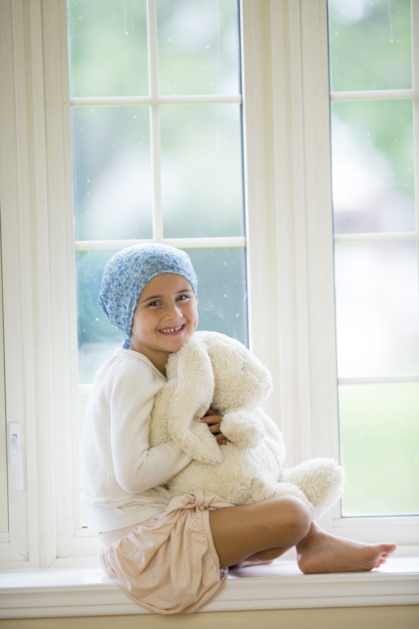 A little girl with cancer is sitting by the window and is looking at the camera. She is holding a stuffed animal.