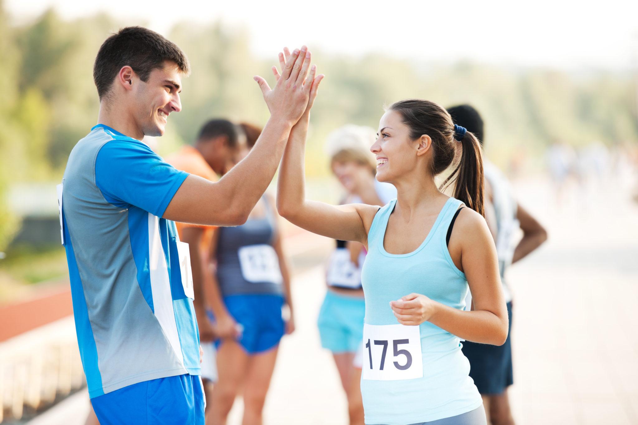 Marathon runners giving high five.