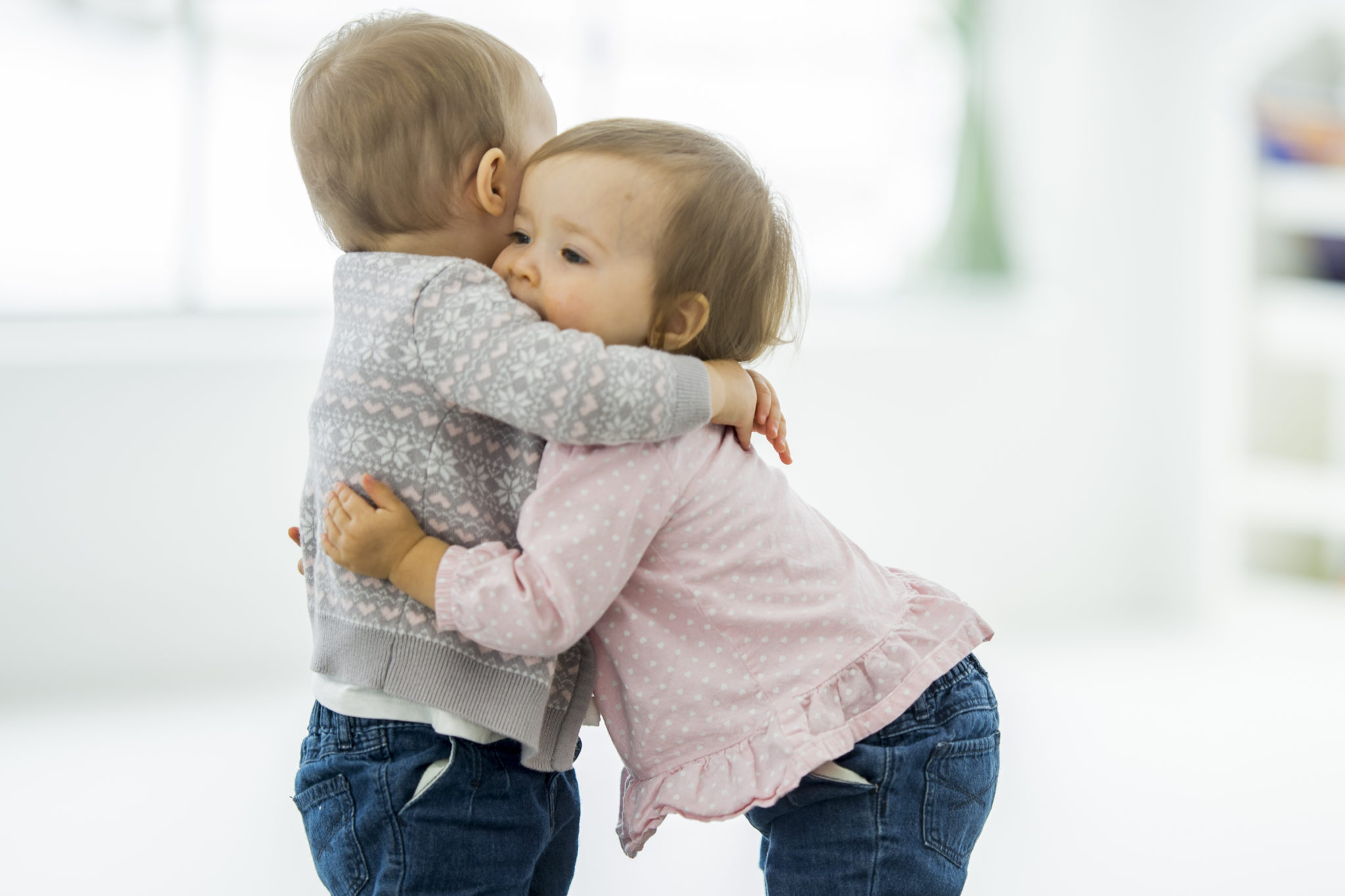 Two twin baby girls are playing together and hugging at daycare.
