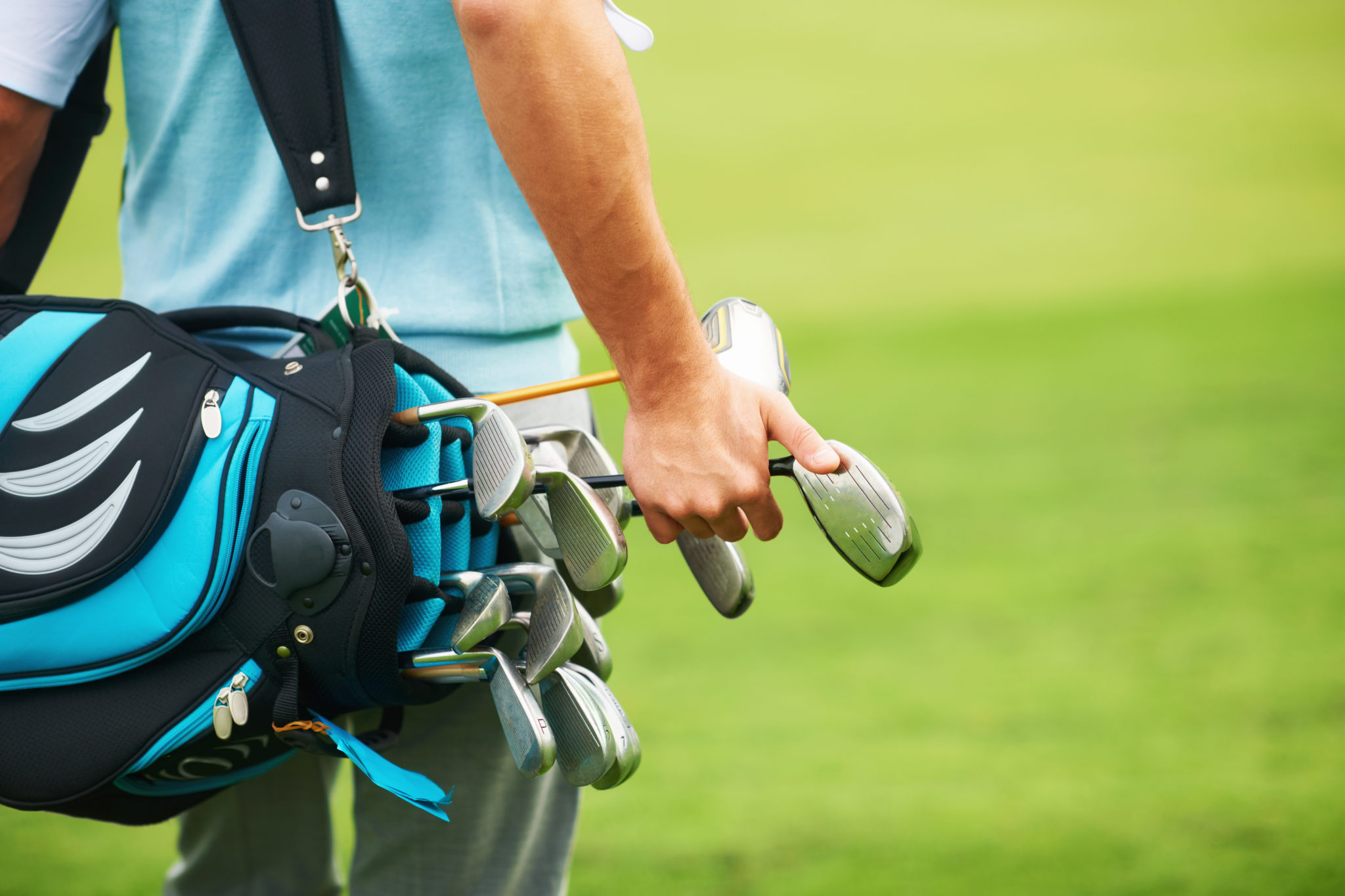 Rear view of a young golfer picking the right golf club out of his bag